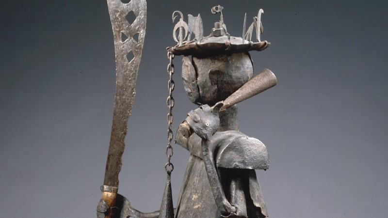 Statue entièrement fabriquée à partir de ferrailles d'origine européenne. Les pieds en fer forgé sont rivés au socle formé d'une plaque en tôle d'acier. Les jambes, barres de fer martelées, sont pourvues de prolongements s'enfonçant dans les pieds auxquels les fixent des rivets. Elles sont reliées au corps par rivetage sur un axe horizontal qui traverse le haut des cuisses. Le corps lui-même est fait d'une forte barre de fer à section rectangulaire. Au niveau des épaules une barre horizontale (percée au milieu pour le passage du cou) s'adapte au corps sur lequel elle est fixée par un énorme clou. Vers le haut, le corps devient un cylindre muni d'un boulon au sommet et destiné à recevoir le cou, tube de tôle qu'entoure un collet et qui supporte la tête. Celle-ci, boule creuse sur laquelle le visage est attaché comme un masque, est coiffée d'un chapeau surmonté par un écrou vissé sur le boulon. Les bras tubes adaptés aux épaules, enveloppent les barres de fer traités plus bas en avant-bras et en mains. Des épaules jusqu'au milieu des cuisses, le coups est revêtu d'une tunique sans manches en tôle mince dont les feuilles, découpées au ciseau, récréent l'ampleur des tuniques de guerre dahoméennes. Sous la tunique, Gou porte un pagne fait d'une épaisse barre de fer aplatie et courbée. La main droite tenait autrefois une clochette et la main droite un grand sabre au fer ajouré. Hauteur : 165 cm.