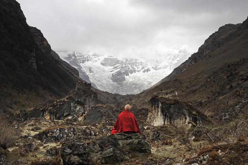 MR 2280 Depuis la plaine de Jango Thang, à plus de quatre mille mètres d'altitude, un moine en méditation devant l'impressionnant glacier du Jomo Lhari (7326m, la montagne la plus élevée du Bhoutan) qui disparaît dans les nuagesJomolhari, 24,037' / 7326 m. Climbed by Spencer Chapman (UK) and Sherpa Pasang (Nepal) on 21st May 1937.