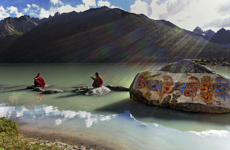 MR 1375-DB 4053 Two Tibetan monks at the banks of the Yilung Lhatso Lake in eastern Tibet. The Lake of Yilung LhatsoThe icy lake of Yilung Lhatso (at 14,000 feet above see level, 4300 meters), not far from Derge was given its name, which means 'Divine Lake of the Mind's Delight,' in memory of a Tibetan princess who passed by this lake on her way to marry one of the ministers of the legendary King Gesar. Her mind was ravished by the place to such an extent that she announced that she would settle there and that the minister could come to marry her there if he wished so.The engraving on the rock reads 'Om Mani Padme Hum', which is the mantra of the Buddha of Compassion, Avalokiteshvara (Chenrezig in Tibetan).Deux moines tibétains au bord du lac de Yiloung Lhatso, dans le Tibet oriental. Sur le rocher, est gravé le mantra du Bouddha de la compassion, « Om Mani Padmé Houng ». Juillet 2005