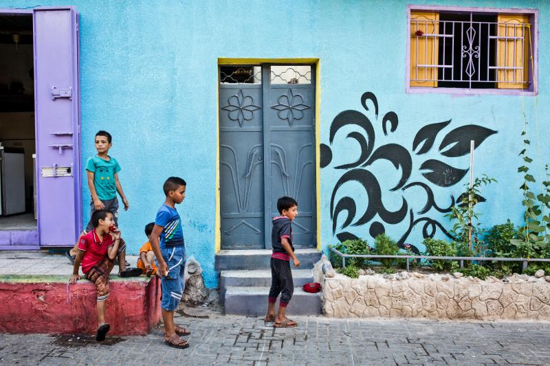 GAZA, Zaytoun: Some boys are playing in the streets of Zaytoun. Behind them, a wall totally blue and purple. Kids of the neighbourhood are very happy about the new look of their streets.  15/08/15  GAZA , Zaytoun : Des garçons jouent dans les rues de Zaytoun . Derrière eux , un mur totalement bleu et violet. Les enfants du quartier sont très heureux du nouveau look de leurs rues . 15/08/15