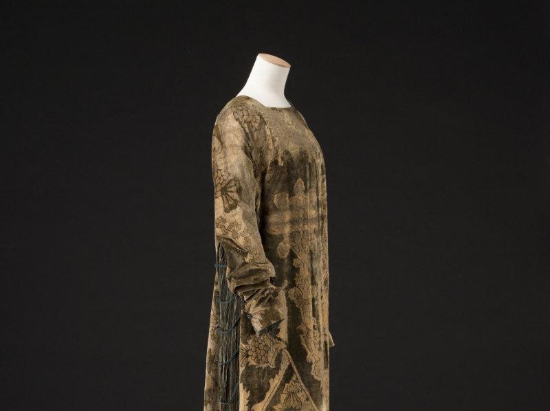 Mariano Fortuny (1871-1949). Robe Delphos. Soie vert bronze, cordonnet en soie noire, perles en verre couleur ambre, perles en verre blanc et noir. Vers 1912-1919. Galliera, musée de la Mode de la Ville de Paris.