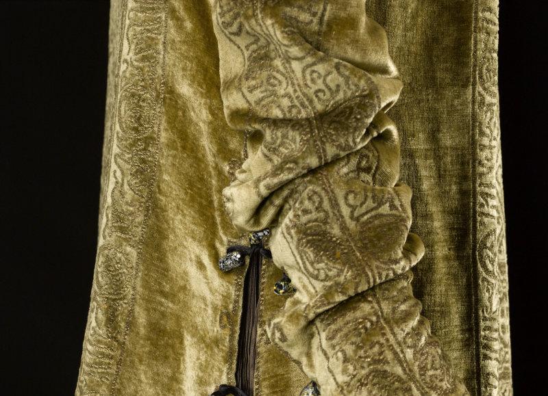 Mariano Fortuny (1871-1949). Robe Eleonora. Velours de soie bronze-vieil or imprimé or. Toile de soie marron plissée. Cordonnet de soie noire, perles en verre noires, blanches et jaunes. Doublure en toile de soie vieil or. Vers 1910. Galliera, musée de la Mode de la Ville de Paris.