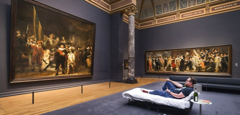 This handout picture released on June 2, 2017 by the Rijksmuseum of Amsterdam shows Stefan Kasper lying in a bed in front of the painting