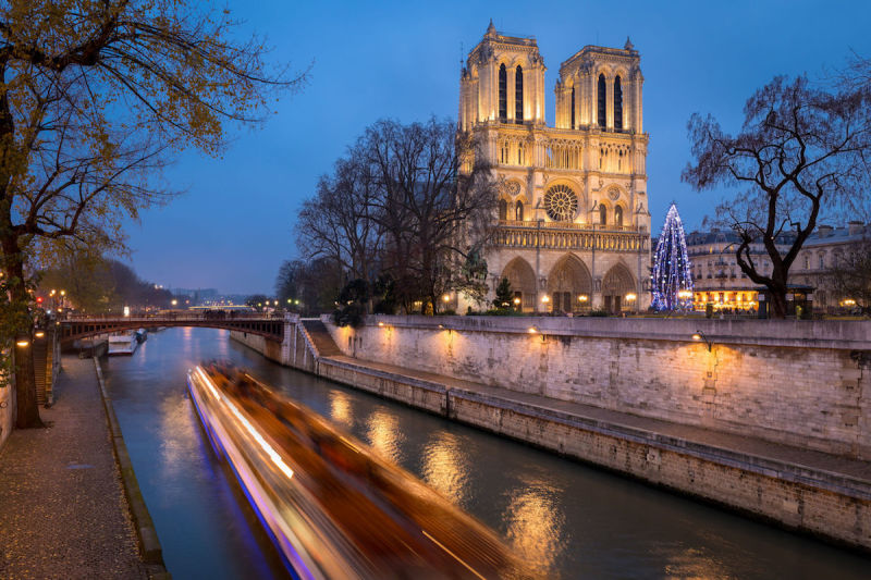 47483617 - christmas tree at notre dame cathedral illuminated in early evening on ile de la cite with passing tour boat on the seine river, paris, france