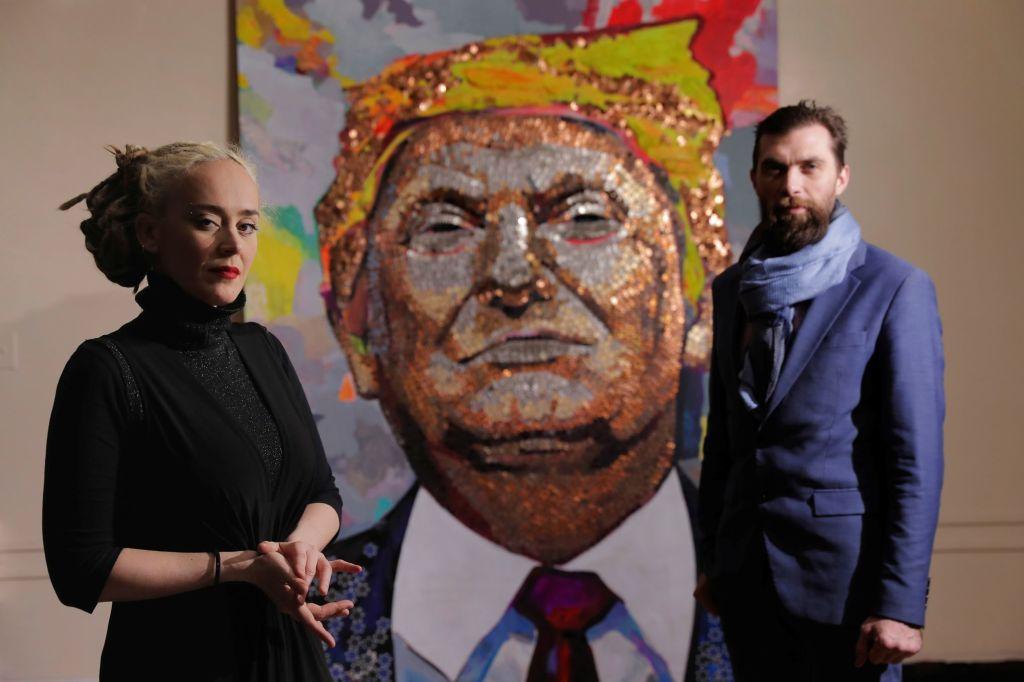 Artists Daria Marchenko and Daniel D. Green pose in front of their portrait of U.S. President Donald Trump made of coins and casino tokens in a classroom in New York