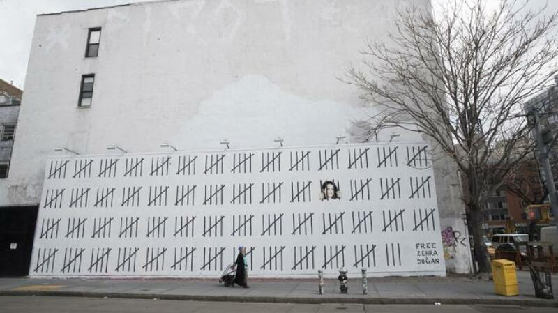A person walks past a mural by British graffiti artist Banksy protesting the imprisonment of Turkish artist Zehra Dogan, Friday, March 16, 2018, in New York. Banksy has created the New York mural protesting the imprisonment of Dogan, an ethnic Kurd jailed after painting the Turkish flag flying over the rubble of a destroyed town. (AP Photo/Mary Altaffer)