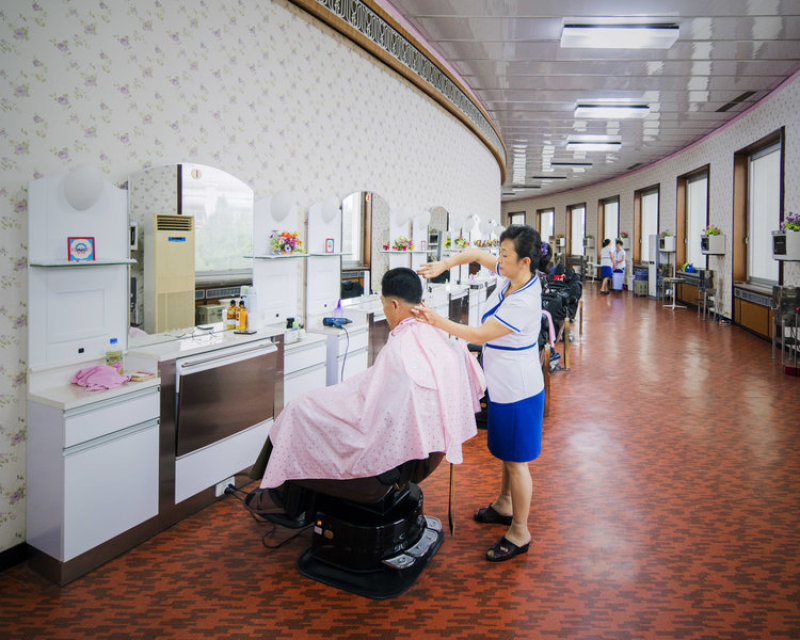 A barbershop inside Changgwang-won health complex, following the curve of the building, and full of vintage design elements such as the pattern-printed flooring and wallpaper, the seats and even the staff uniforms.