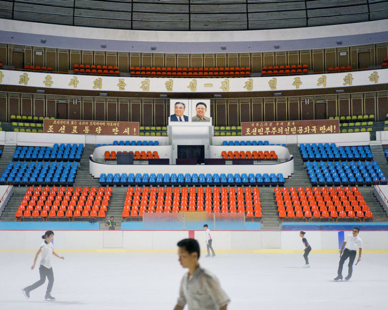Pyongyang Ice Rink, interior. Enthusiasts of various levels practice their skating skills, under the vast conical roof and surrounded by warm harmonious colors.