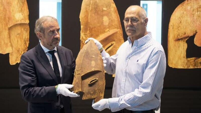 Hermann Parzinger (L), President of the Prussian Cultural Heritage Foundation, and John Johnson from the Chugach Alaska Corporation, hold a wooden object from Berlin's Ethnological Museum during a restitution ceremony in Berlin on May 16, 2018. Germany has returned nine artefacts belonging to indigenous people in Alaska, after determining that they were plundered from graves. The Prussian Cultural Heritage Foundation, which oversees museums in the German capital, said the burial objects were brought to Berlin in 1882-1884 on commission by the then Royal Museum of Ethnology, but