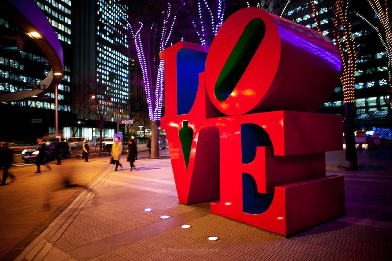 TOKYO, JAPAN, 26 JANUARY - Shinjuku - Salarymen are walking in front of the famous LOVE sculpture created by Robert Indiana. This business area of shinjuku is made by very high tower building - January 2012