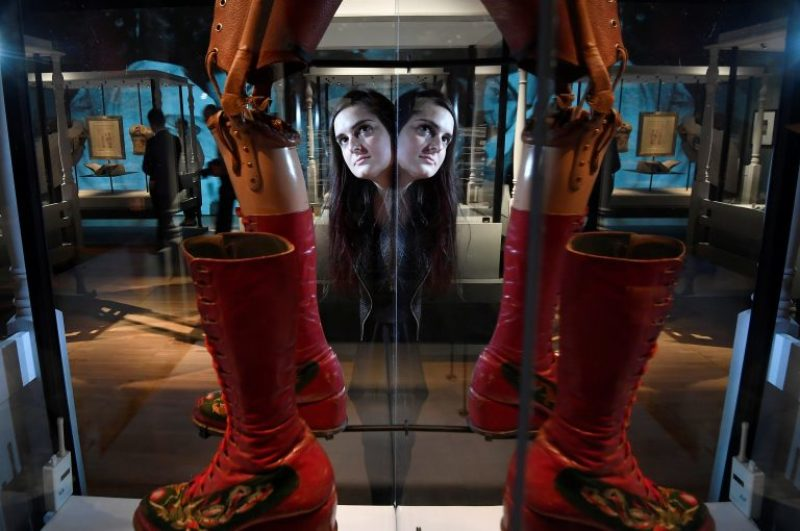 An employee poses as she views a prosthetic limb and boot, forming part of Frida Kahlo -Making Herself Up