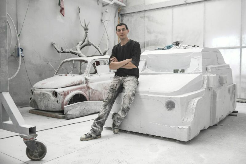 Italian artist Nazareno Biondo poses on his ongoing sculpture made with Carrara's marble representing the iconic car Fiat 500, on May 16, 2018 in Cafasse, near Turin. RESTRICTED TO EDITORIAL USE - MANDATORY MENTION OF THE ARTIST UPON PUBLICATION / AFP PHOTO / MARCO BERTORELLO / RESTRICTED TO EDITORIAL USE - MANDATORY MENTION OF THE ARTIST UPON PUBLICATION - TO ILLUSTRATE THE EVENT AS SPECIFIED IN THE CAPTION