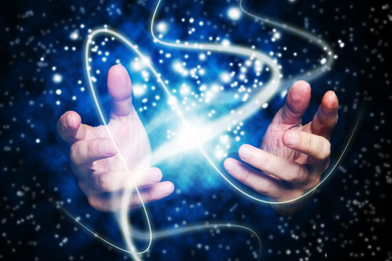 open hands with magic lights effects against a space background