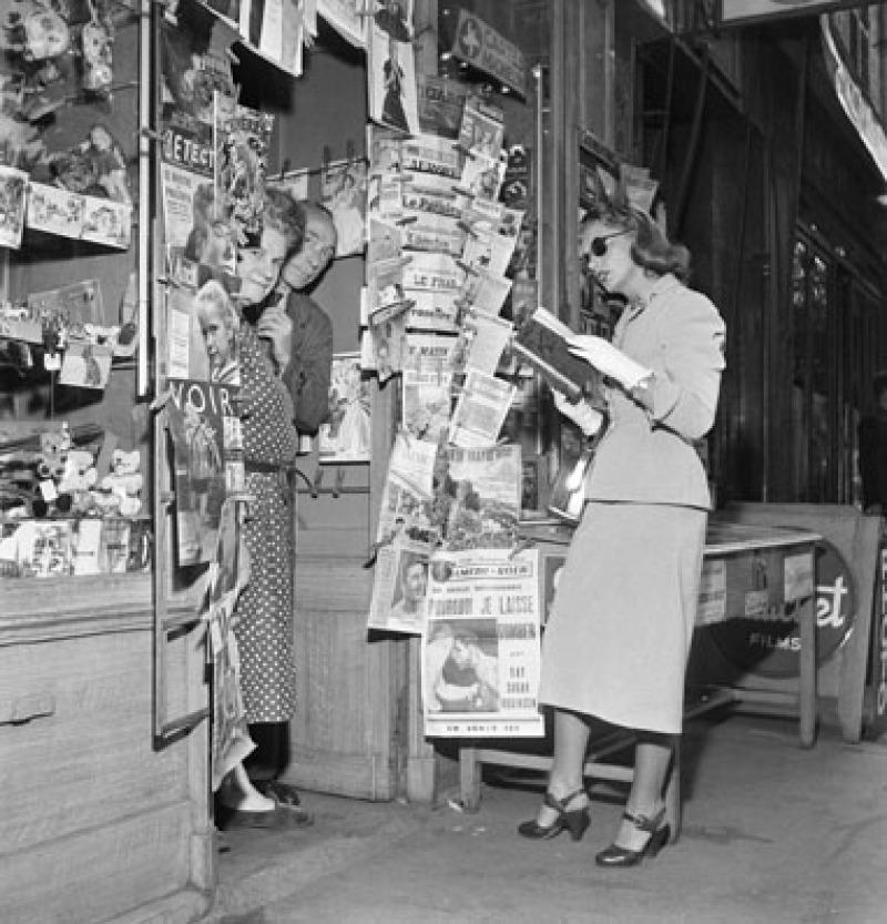 Irène Corday (1919-1996), actrice française, devant un kiosque à journaux. Paris, juin 1952. Photographie de Roger Berson.