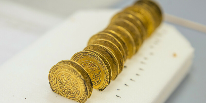 This handout picture released by the University Lumiere Lyon II on November 14, 2017, shows golden dinar coins on September 21, 2017, in Cluny, central France.  Scientists from the University of Lyon II and the French National Centre for Scientific Research (CNRS) found a medieval treasure of over 2,000 coins from the 12th century as they were probing an angle of the former Cluny Abbey. / AFP PHOTO / University Lumiere Lyon II / Alexis GRATTIER / RESTRICTED TO EDITORIAL USE - MANDATORY CREDIT