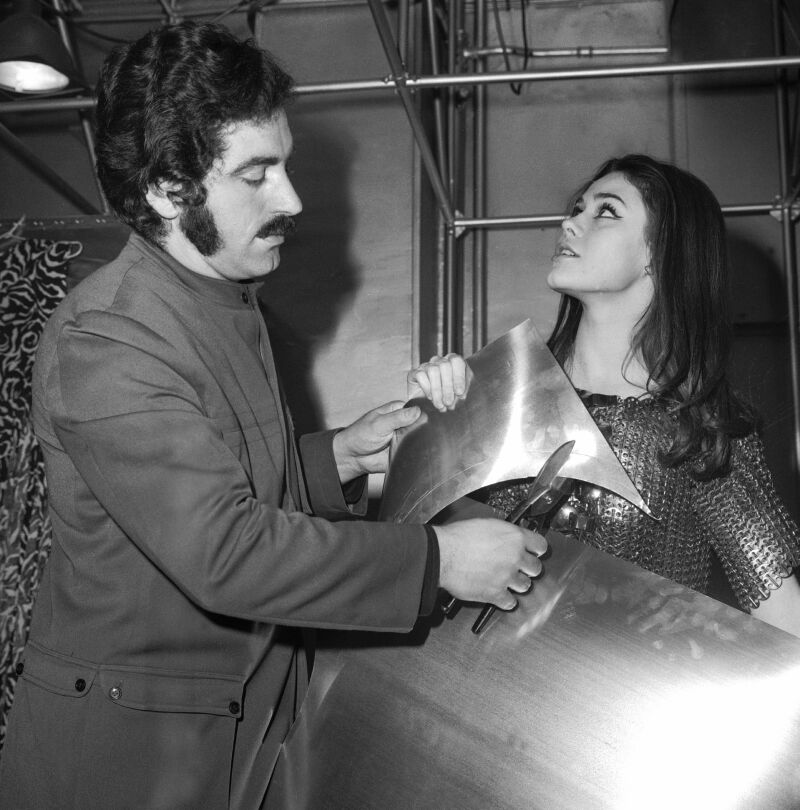 FRANCE - JANUARY 01:  The fashion designer Paco RABANNE with a young cover-girl, Corinne PICCOLI. He was carrying out a demonstration of metal-cutting in front of her.  (Photo by Keystone-France/Gamma-Keystone via Getty Images)