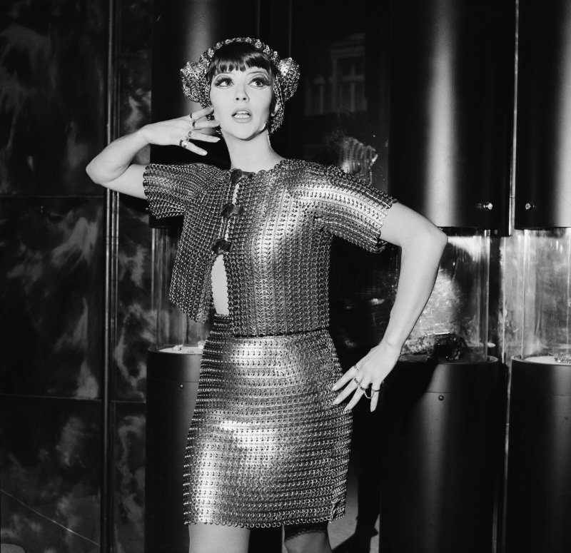 Jackie Bowyer wears a silver chainmail bolero with matching miniskirt by Paco Rabanne, 7th November 1967. She is modelling it at the opening of the new Jones jewellery shop in Brompton Arcade, Knightsbridge, London. (Photo by Peter King/Fox Photos/Getty Images)