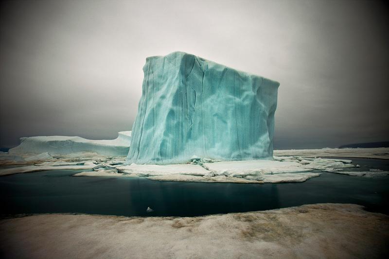 Les icebergs se forment  lorsqu'ils  se détachent  des glaciers ou  des plateformes  de glace. Ces  dernières, véritables barrières  flottantes, ne contribuent  pas à  la montée  de l'océan  ; attachées  à  la côte, elles  ralentissent  l'avance  des glaciers qui eux  sont  soumis  à  la gravité  et avancent  en suivant  le sens  des pentes. Les barrières  de glace ont  pratiquement disparu  de l'Arctique.  ©Sebastian Copeland