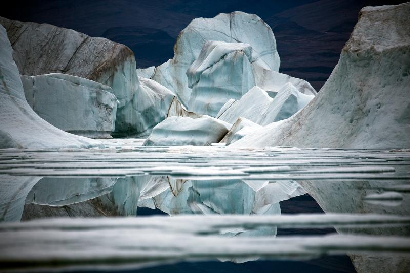 La densité de l'eau augmente avec le froid.  Et l'eau salée est encore plus lourde. La combinaison de la masse et de la densité de l'eau autour des icebergs protège sa surface des perturbations du vent, ce qui explique les reflets proche de la perfection d'un miroir. ©Sebastian Copeland