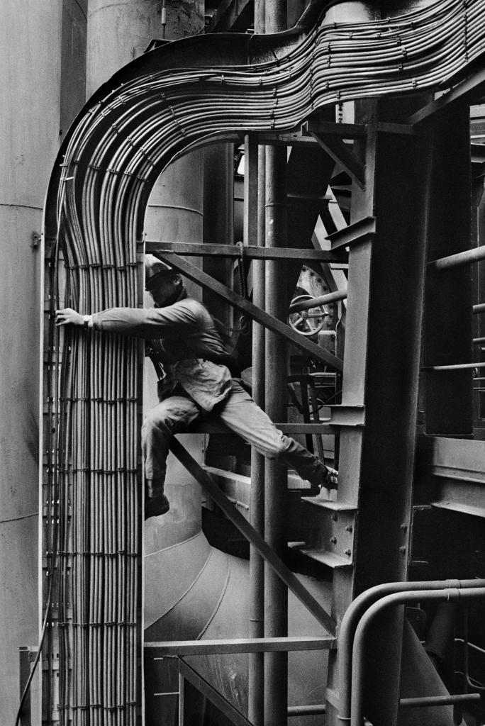 Un ouvrier répare des tuyaux qui font partie du système de câblage électronique autour duhaut fourneau numéro 4. Dunkerque.France, 1987