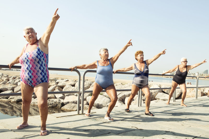 Active seniors stretching during outdoor fitness class