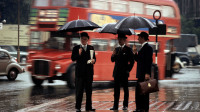 ENGLAND. London, 1964.  Three gentlemen wait for a bus in the rain on Hyde Park corner in London.