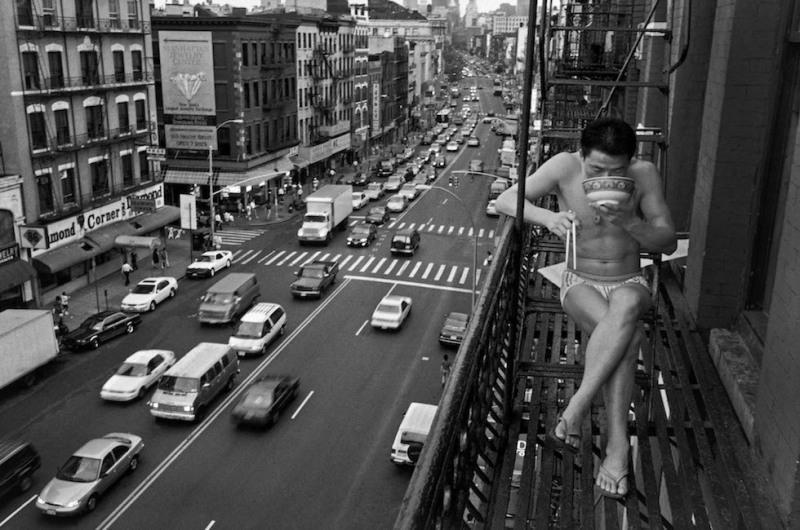 USA. New York City. 1998. Un immigrant nouvellement arrivé mange des nouilles dans une sortie de secours. New York, États-Unis. A newly arrived immigrant eats noodles on a fire escape.