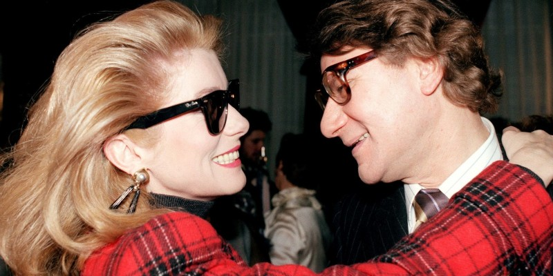 (FILES) This file photo taken on January 28, 1987 shows French actress Catherine Deneuve  with French deigner Yves Saint Laurent, after his haute-couture spring-summer fashion show. - French actress Catherine Deneuve, who has just turned 75, decided to auction off her Yves Saint Laurent designer clothes at Christie's auction house at the end of January 2019 in Paris. (Photo by PIERRE GUILLAUD / AFP)